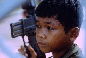 A very young Cambodian soldier during operations against the communist Khmer Rouge in Cambodia. The Cambodian Civil War was a civil war in Cambodia fought between the forces of the Communist Party of Kampuchea (known as the Khmer Rouge, supported by North Vietnam and the Viet Cong) against the government forces of the Kingdom of Cambodia and, after October 1970, the Khmer Republic, which had succeeded the kingdom (both supported by the United States (U.S.) and South Vietnam). Photograph by Mark Godfrey