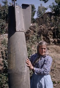 A Lebanese woman holds a bomb-like casing dropped by Israeli aircraft during bombing strikes in southern Lebanon in 1974. During 1974, and just prior to the 1975 civil-war in Lebanon, a stealth-war was raging in southern Lebanon between Israel and Palestinian groups that included regular bombing strikes by Israeli aircraft. Photograph by Mark Godfrey