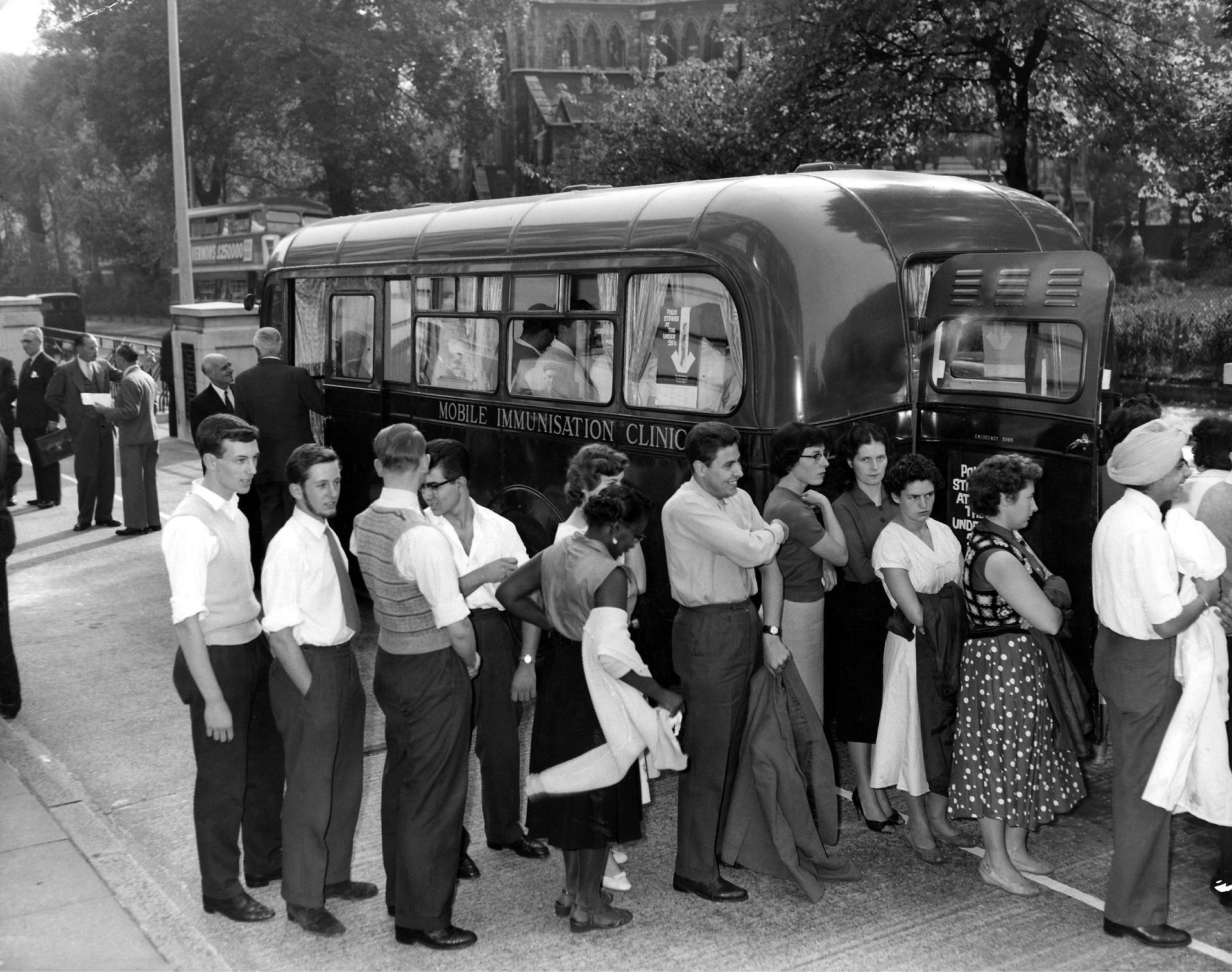 Factory workers line up to have the first treatment at the new Mobile Immunisation Cliinic, outside Cossor House, Highbury Grove, London N5 1959 A mobile clinic has been made available by the LCC to make it easy for young people working in factories and offices in London to be vaccinated against poliomyelitis. A school bus has been converted at a cost of about £300 and has started to make it's calls this week in North London, whee an anti-Polio campaign is in progress.