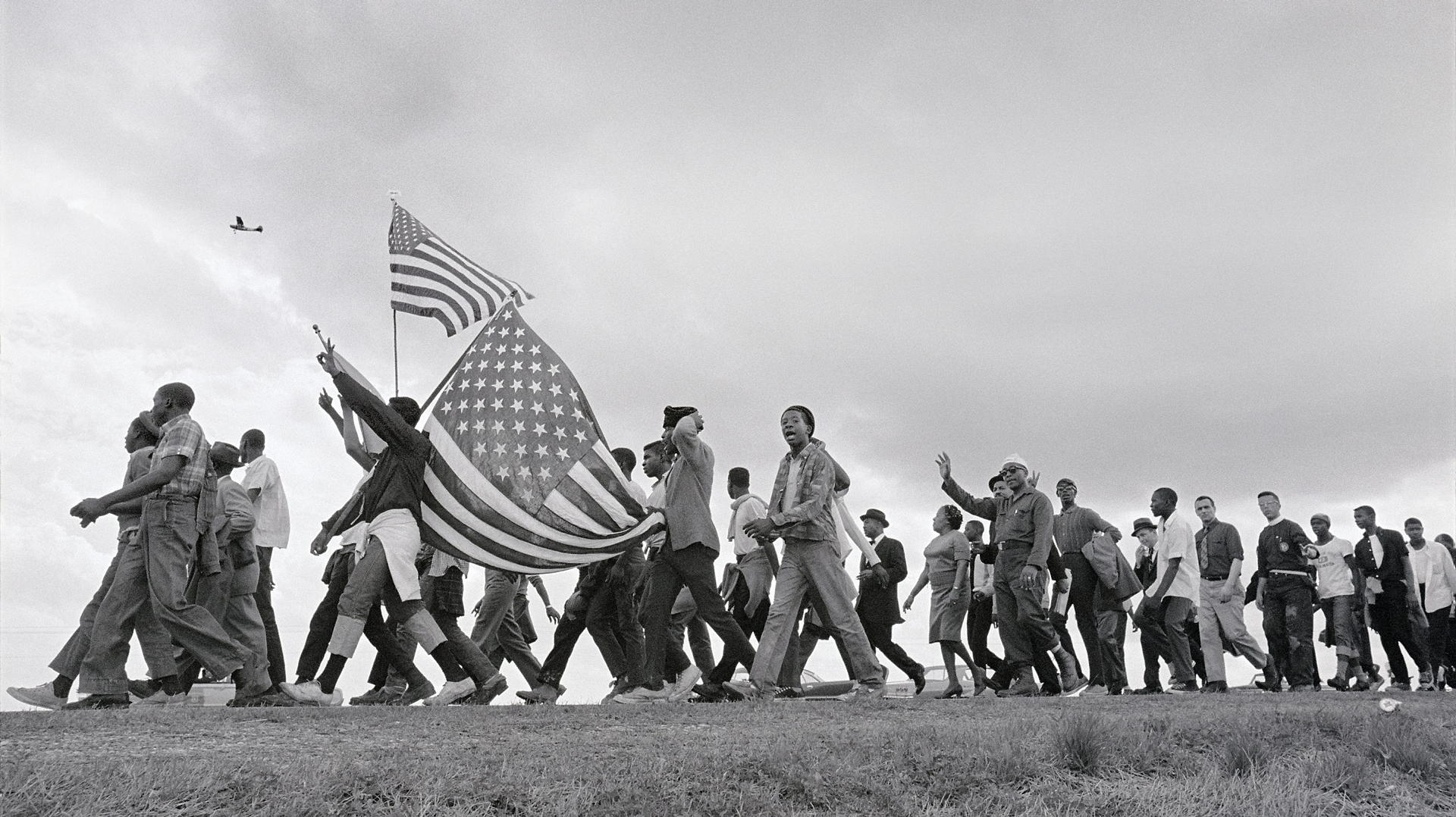 TKS1676432 Alabama: March 21, 1965. Selma to Montgomery March for voting rights: Marchers and flags cross the horizon. Airplane is reconnaissance plane of Alabama National Guard on lookout for threats to march.
