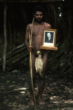 A member of the Iounhanan tribe from the island of Tanna (Vanuatu) who worship the Duke of Edinburgh. Their treasure and the 'one true cross' is this signed photograph which Prince Phillip kindly provided. The tribe's fervent wish is that he will come and live with them and wives, like the girls pictured, would be available to him should he wish to change his marital status. Photograph by Colin Jones